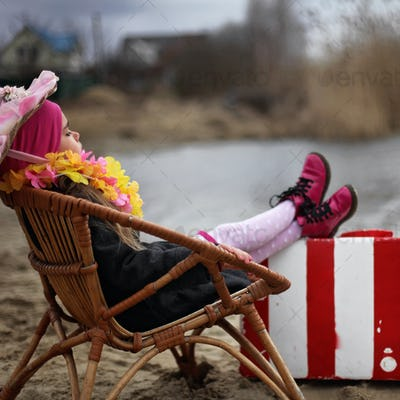 5-6 years old girl in a coat and flowers garland sitting on a beach