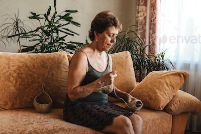 Woman crochets napkin at home.