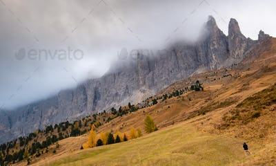 Dolomite mountain peaks covered in fog during sunrise