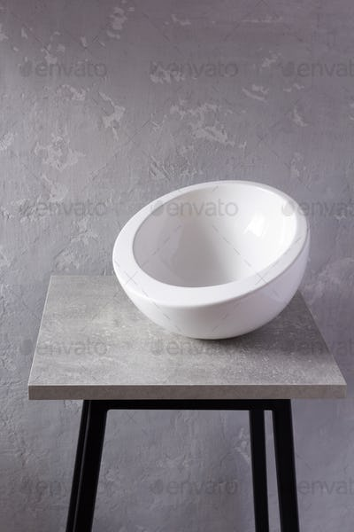 Empty white bowl or dishe at grey table or stool. Kitchen dishware and tableware