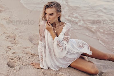 Gorgeous blond woman with perfect tan body lying on send near water in white dress.