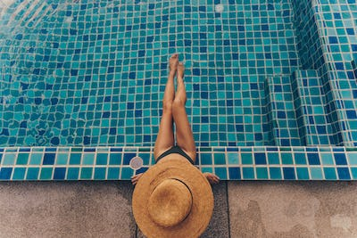 Top  view of graceful woman in swimsuit and straw  hat sitting near the pool.