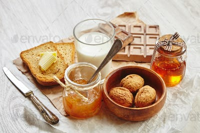 Side view of breakfast set with jam, bread, butter, walnuts and milk