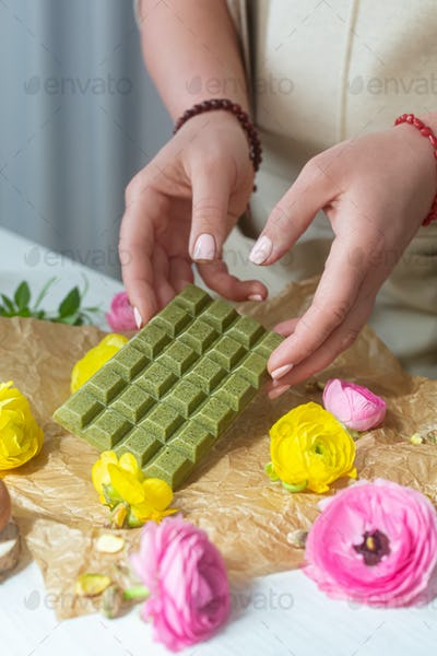 Woman holds organic matcha green chocolate with natural ingredients