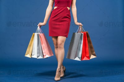 Closeup up Legs of Happy young Asian woman carrying multi color shopping bags