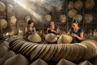 Group of Vietnamese female craftsman making the traditional vietnam hat