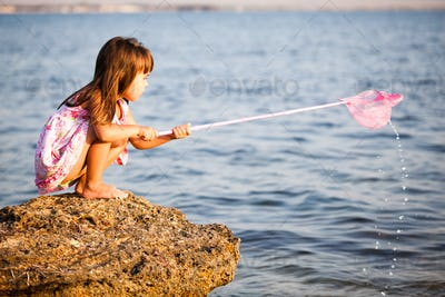 Small smiling girl in bright swimvear standing in sunshine and looking at little stone with blue sky