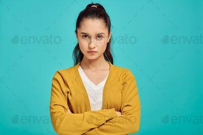 Serious woman portrait, blue background, emotion