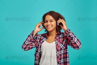 Cute young woman in headphones, positive emotion