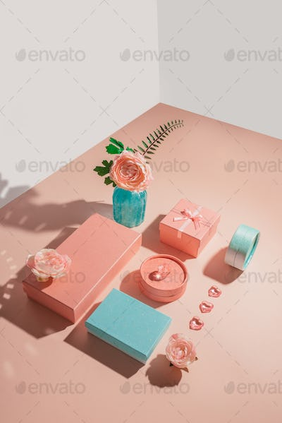 Festive geometric arrangement of gift boxes and flowers in pastel colors with sunny shadows