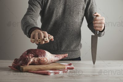 Man holds letters lamb with knife in hand