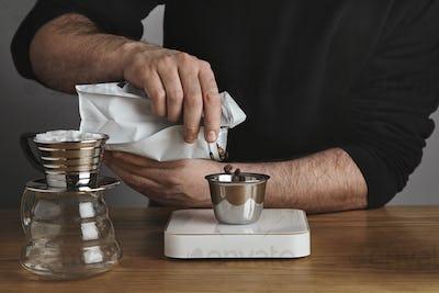 Brutal barista in black sweatshot pours roasted coffee beans