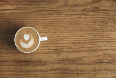 Top view cup with cappuccino on wooden table