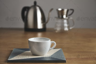 White coffee cup in front of teapot and drip coffee maker