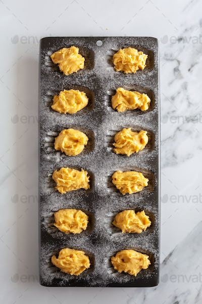 Top down view of raw madeleine cake dough in a baking tin, on white marble background