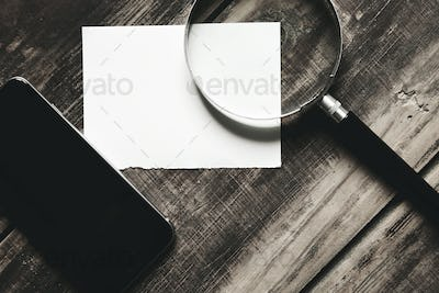 side view smartphone, magnifier and paper on black table