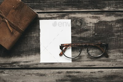 Notebook, glasses, paper on black table