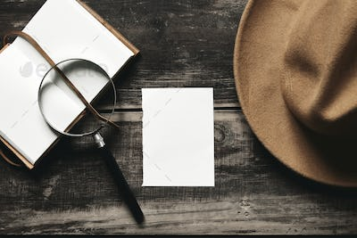 Opened notepok, hat, magnifier paper on black table top