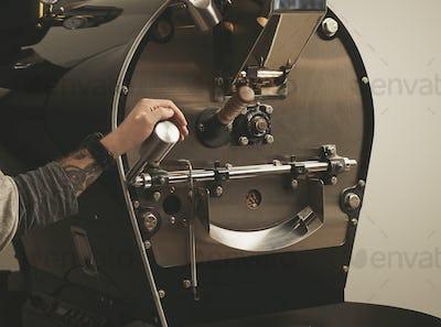 Tattooed hand pulls lever in coffee roasting machine