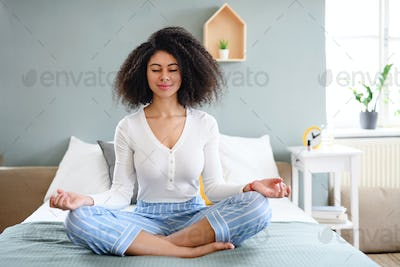 Portrait of young woman indoors at home, doing yoga exercise.
