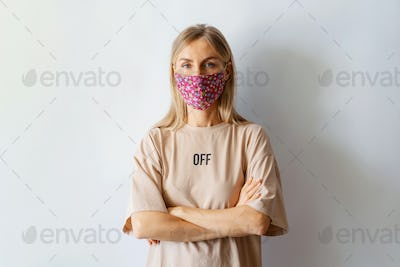 portrait on a pale background of a Caucasian woman in a protective medical textile handmade mask.