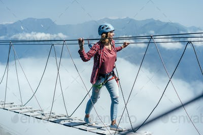 A happy woman walks on a suspension bridge high in the mountains at the level of a cloud.