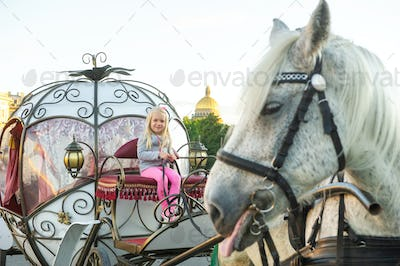 a child sits in the driver's seat in an old carriage on Palace Square in St. Petersburg