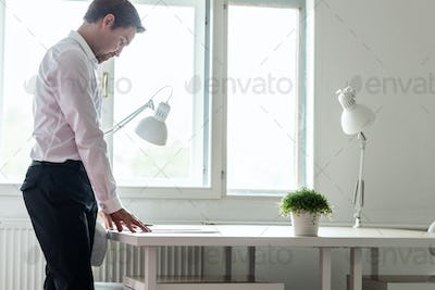 Young businessman standing at his desk reading a contract