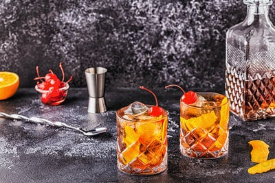 Old fashioned cocktail with cherries and orange twist.