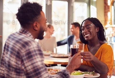 Smiling Young Couple On Date Making Toast Before Enjoying Pizza In Restaurant Together