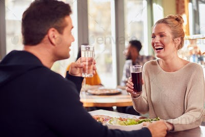 Smiling Couple On Date Enjoying Pizza In Restaurant Together