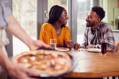 Smiling Couple On Date In Restaurant Together With Waiter Holding Pizza In Foreground