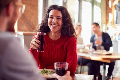 Smiling Young Couple On Date Enjoying Pizza In Restaurant Together