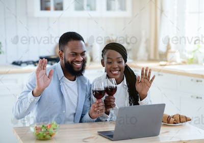Online Party. Cheerful Black Couple Making Video Call With Laptop In Kitchen