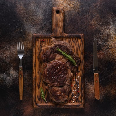 Grilled beef steak with spices on a wooden board.