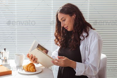 Side view of happy young beautiful woman reading book while having morning breakfast with coffee and