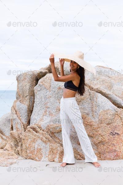 stylish woman wearing large big giant straw hat on rocky tropical beach