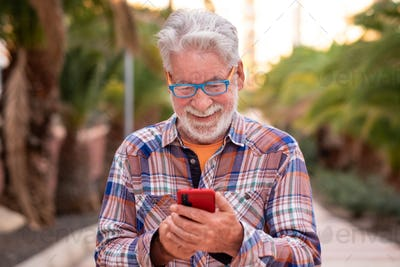 Smiling senior man using technology with smartphone standing outdoor in a public park at sunset