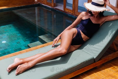 perfect skin woman in black vintage old bikini lies on green sun bed