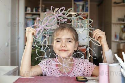 Girl doing wreath with toilet roll tube via online master class, zero waste Easter celebration