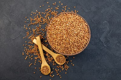 top view brown buckwheat inside plate with pair of spoons on dark background cereals groats seed