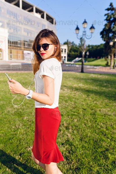 Vertical portrait of a standing young girl holding a smartphone and listening to music on earphones