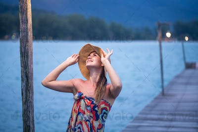 girl in hat on the pier in the evening