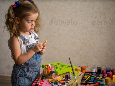 the little girl in the process of paints