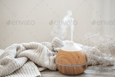 Cozy home composition with air humidifier, knitted element and dried flowers copy space.