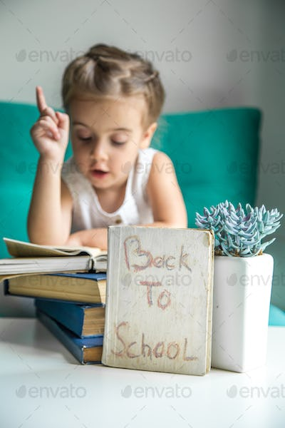 girl sitting with a book in hand back to school