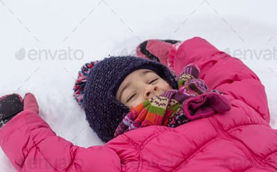 Little girl in a pink jacket and hat lies in the snow close up.