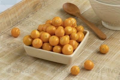 Bowl with fresh orange goldenberries close up