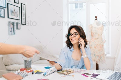 A cute brunette girl in a blue shirt is siiting at the table in workshop. She is speaking on phone