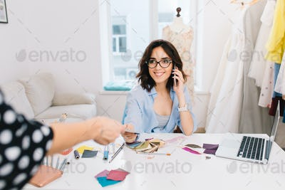 A smiling brunette girl in a blue shirt is working in workshop. She is sitting at the table and
